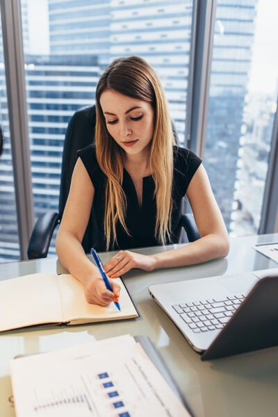 Concentrated businesswoman working writing notes in notebook sitting at desk in office.